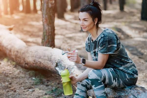 Frau nach dem Sport, mit Proteinriegel und Aminosäuren-Shake