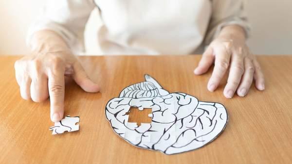 Alter Mann legt Puzzle eines Gehirns