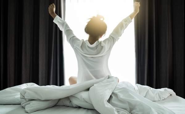 Frau steht früh am Morgen auf