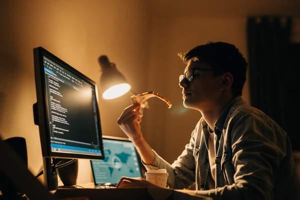 Ursachen von Schlafstörungen - Mann nachts am PC mit Pizza und Kaffee