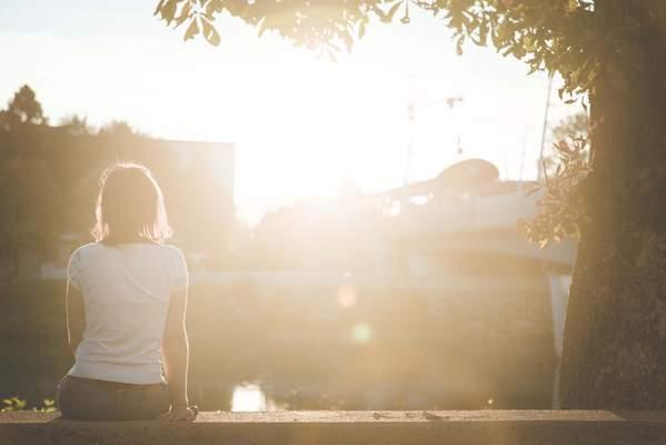 Frau sitzt in der Sonne und tankt Vitamin D