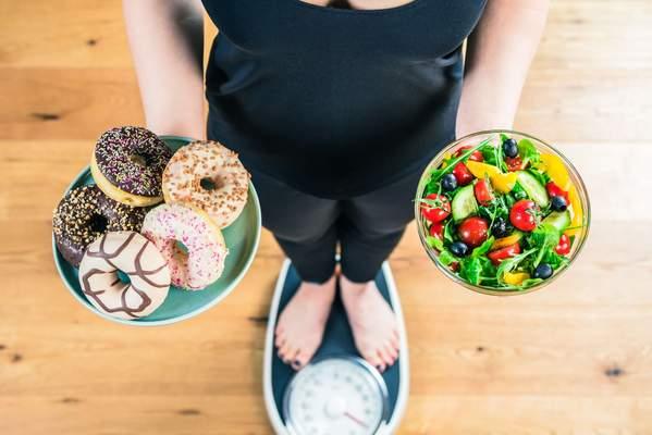 Symbolbild Ernährungsumstellung: Frau auf Waage mit Donuts und einem Salat