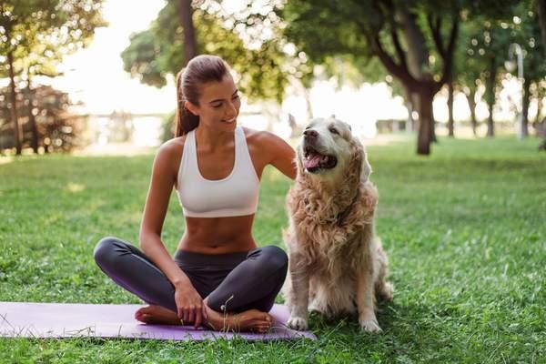 Frau entspannt beim Yoga mit Hund im Park