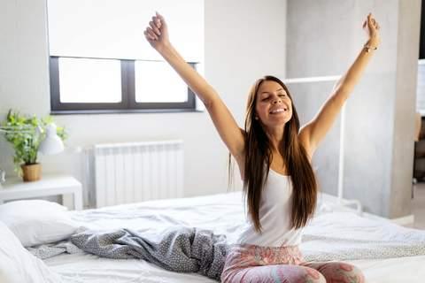 Frau glücklich und ausgeschlafen morgens im Bett